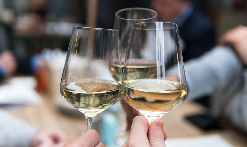 White wine glasses being cheered