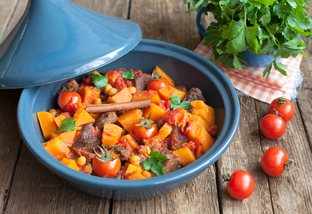 Moroccan Lamb Tagine with chickpeas, pumpkin and cherry tomatoes on a wooden table. Selective focus