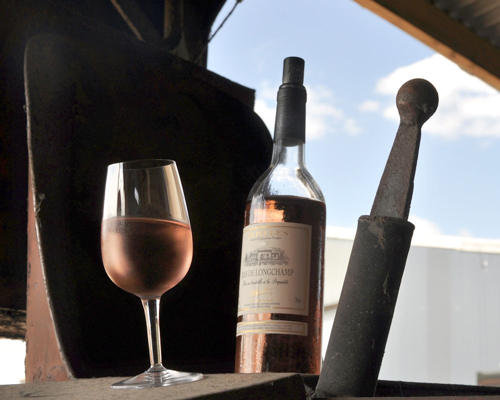 Chilled rosé wine in a glass next to bottle of rosé wine